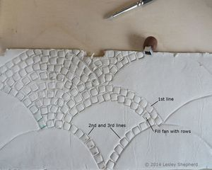 Stamping fan patterns of cobblestones into air dry clay at the front of a dollhouse scale shop. - Photo © 2014 Lesley Shepherd