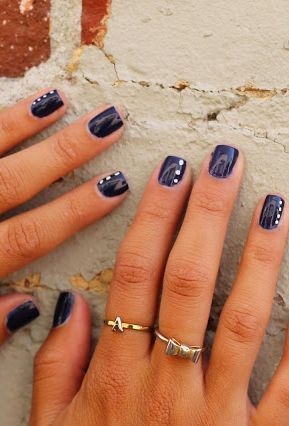 Navy blue nails with white dots.