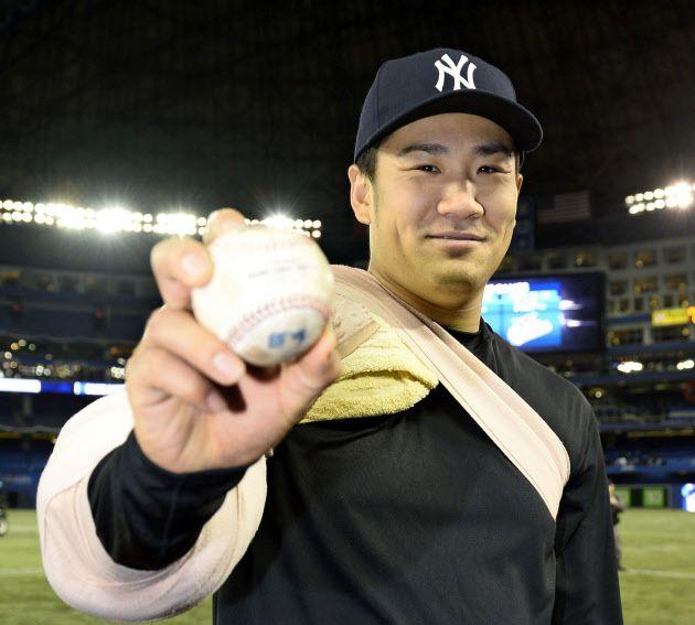 ブルージェイズ戦でメジャー初勝利を果たし、ウイニングボールを手に笑顔のヤンキース・田中将(4日、トロント)=共同