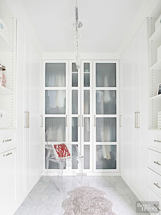This sleek space shows off the splendors of specialized storage. Shirts and pants on hangers stack two rows high behind frosted-glass doors so you can just make out what's inside, while tall, solid doors keep the closet clutter-free. Open shelves showcase pretty purses and silk scarves above a sneaky tilt-out hamper, while a Lucite chair and sheepskin rug drape the closet in luxury./