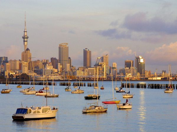 The morning sun rises on the Auckland city skyline and a cluster of boats moored in the inner harbor. Auckland, on North Island, is the largest city in the country.