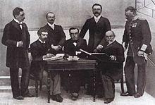 Photo d'une partie du Comité International Olympique réunis autour d'une table pour signer des documents.