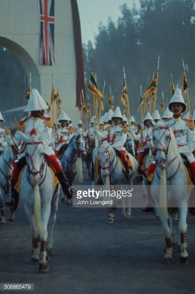 A group of Royal Guards mounted on horses and holding flags at Triumphant Arch in Addis Ababa during Queen Elizabeth II's visit to Ethiopia in February of 1965.