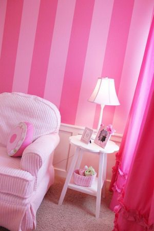 Pink striped baby girl nursery walls with ruffled fuchsia curtain panels and chenille chair and ottoman