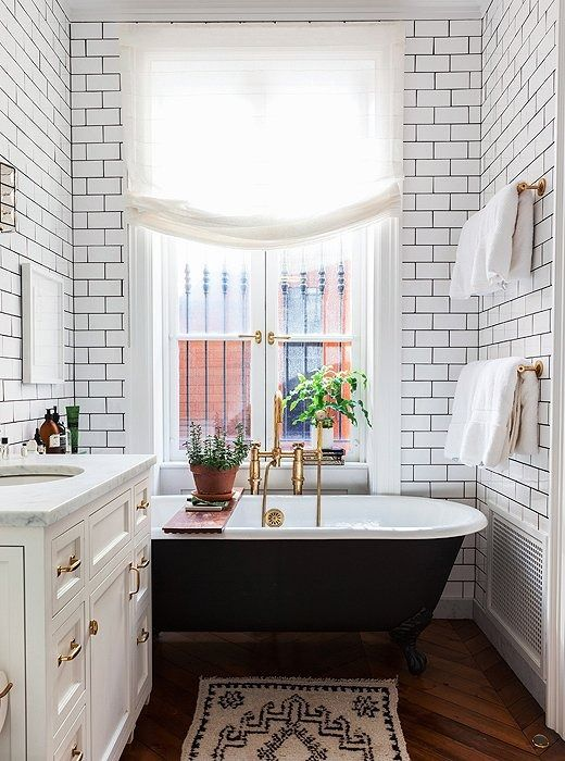 This petite bathroom feels light and airy thanks to floor-to-ceiling white subway tiles with black grout, marble counters atop white cabinets, and gleaming brass hardware on the bathtub, sink and walls.