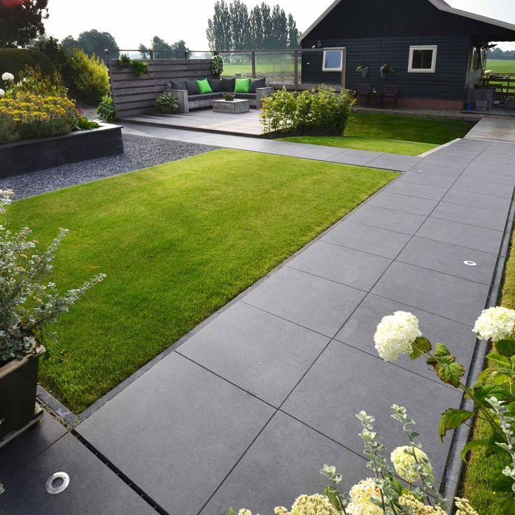 Moderne tuin met grote grijze tegels.