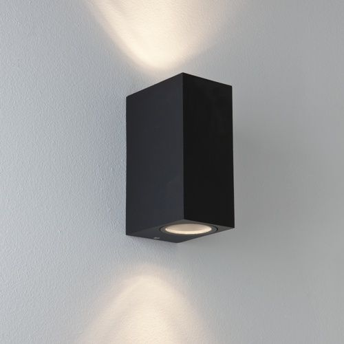 outdoor wall light finished in black with 2 light heads facing up and down with protective glass lenses on