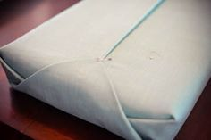 wrap cushion like a present, then pin. finish it with a button and hand stitching.