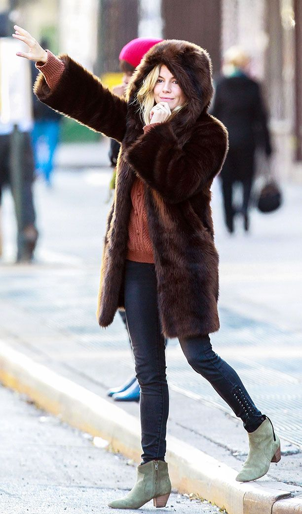 Actress Sienna Miller hails as cab bundled up wearing a hooded fur coat in New York City