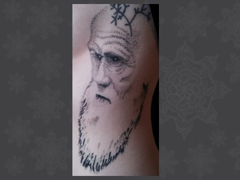 This is my Darwin tattoo. My first tattoo was a simplified version of his tree of like (you can see most of it in the picture).  I wanted something more, but something a bit different from a standard portrait.  This is a stippling tattoo (made of dots).  It was done by Kane of Fox Body Art in Melbourne.