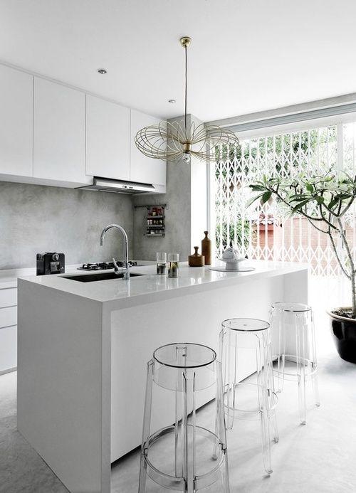 reforma cocina con isla central para fregadero y barra, muebles lacados en blanco, frente y suelo acabado micromento