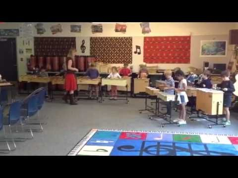 """Kindergarteners playing the Orff bells - cute game idea with 3 different colored hula hoops on the floor for different types of instruments. Students get to play and practice watching a """"conductor""""."""