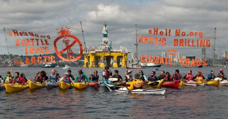 Paddling activists met the Royal Dutch Shell drilling rig as it arrived in the Port of Seattle. The Space Needle is visible behind the hulking yellow rig. (Photo: Reuters)