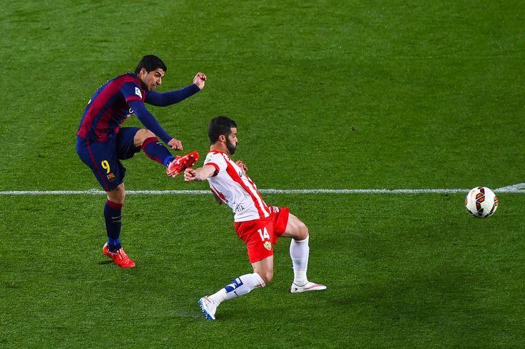Luis Suarez of FC Barcelona scores his team's second goal under a challenge by Jose Manuel Casado of UD Almeria during the La Liga match between FC Barcelona and UD Almeria at Camp Nou on April 8, 2015 in Barcelona, Catalonia.