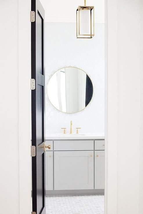 A black door with brass knob opens to a gold and gray bathroom filled with a gray shaker washstand adorned with brushed brass hexagon knobs topped with white quartz fitted with a sink and a Kohler brass faucet placed under a round brass mirror, Rejuvenation Metal Framed Mirror, lining a wall clad in white glass tiles illuminated by a rectangular brass cage lantern, Williamson Lantern.