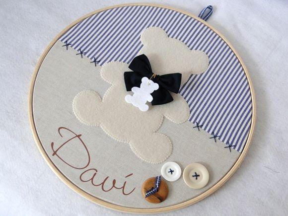 Quadro Porta Maternidade modelo Bastidor Urso    Confeccionado em tecido e feltro, decorado com botões plásticos e em madeira e personalizado com o nome do bebê.    O quadro mede 30 cm de diâmetro e pode ser feito nas cores e estampas que desejar! R$ 180,00