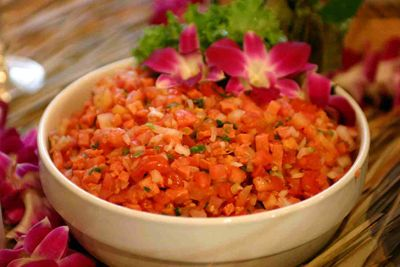 Lomi Lomi Salmon - Lomi lomi salmon is an appetizer that appears on the menu of nearly every Hawaiian luau. It is a mixture of salted salmon, fresh tomatoes, and fresh onions and it is often served on a bed of crushed ice to keep it chilled and tasting fresh.