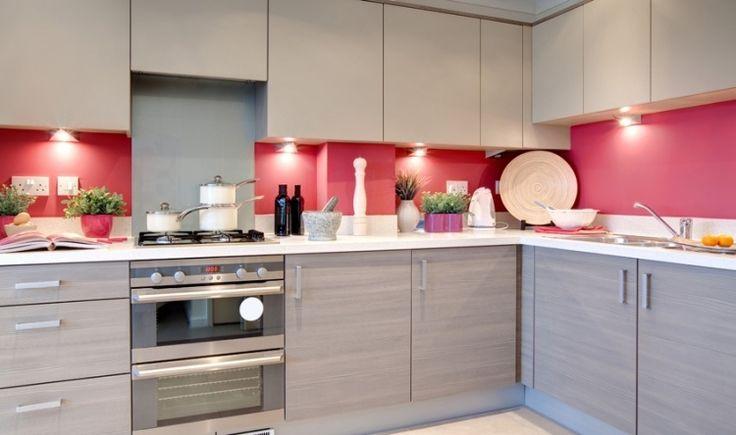 des armoires en gris clair et un dosseret de cuisine rose