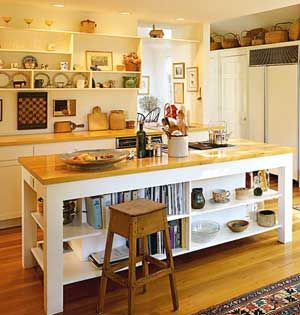 An butcher block island with book and display shelves beneath and white display shelves above counters in kitchen.