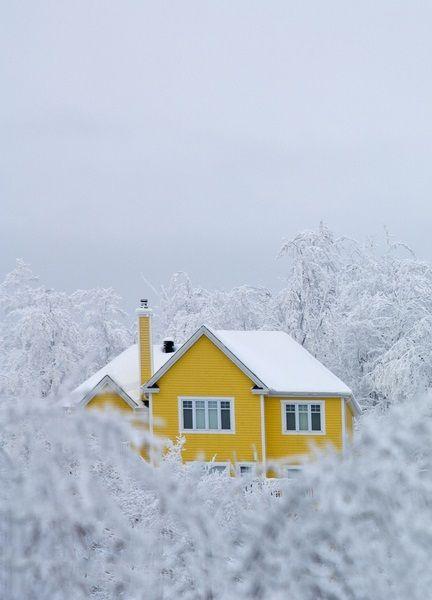 Une petite maison jaune perdue dans la neige