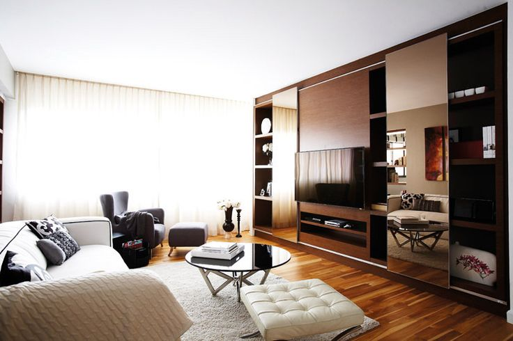 Sliding mirrored panels that divide the living room shelves into display n storage area