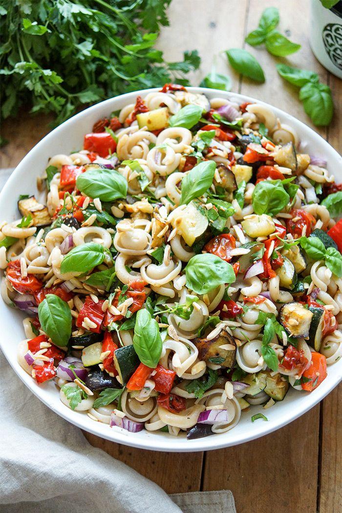 Gesunder Sommer Nudelsalat mit geröstetem Gemüse (Paprika, Zucchini, Aubergine und Cherry-Tomaten), getrocknete Tomaten, geröstete Mandelsplitter und frische Kräuter. Vegan