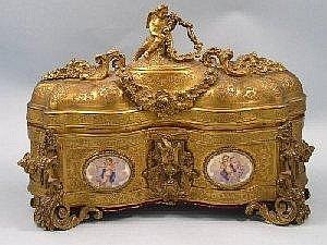 Late 19th century French ormolu jewellery casket, of serpentine outline, the domed cover engraved and cast with flowers and scrolls, surmounted by the figure of a winged angel holding a vacant shield for a picture, suspended with floral swags, a similarly engraved body set with four oval porcelain plaques depicting winged cherubs holding flower garlands, the corners set with leaf scrolls and rams head masks on four scrolled feet, enclosing a red velvet lined interior, 29cm wide x 20.2cm high