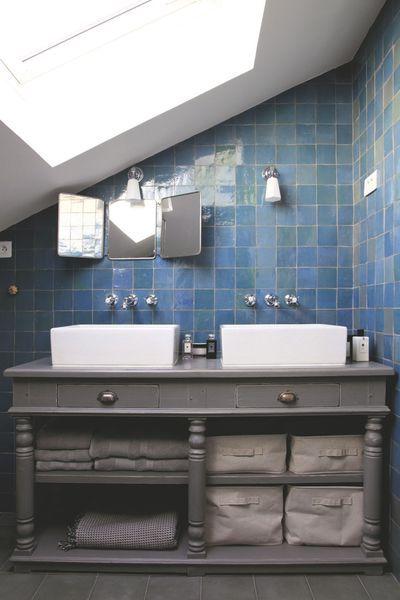 Dans cette petite salle de bains, le meuble avec double vasque se loge sous le rampant de toiture.