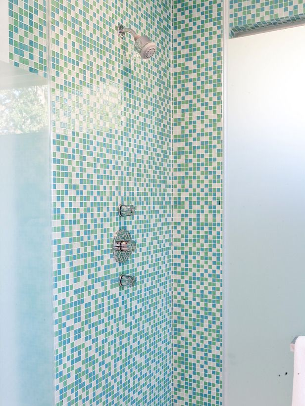 Krise Michelini used blue and green mosiac tile on the walls and small white subway tiles on the shower pan to create the beach vibe her client requested.