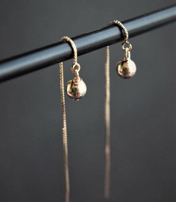 Minimalist 14k gold filled or sterling silver thread earrings with a pendant 6 mm beads. The earrings measure about 3.5 in total length and are designed to drop approximately 2 below the ear. You can adjust the length of your earrings by pulling the chain through your ear. ................... SUMMARY  + 14k Gold filled or Sterling silver thread and beads. + Approximatively 3.5 inches + Adjustable Length + Sold By the Pair. + Handmade.  + Shipped in a Nice little Gift Packaging…