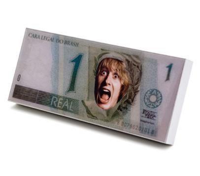 Muito divertido e super em conta, é esse presente super original - um porta retrato que reproduz uma nota de 1 real. Você encaixa uma foto bem no centro da nota e brinca com a figura central da nota do Banco Central do Brasil.