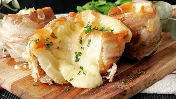 Recipe with video instructions: Filled with cheese and wrapped in bacon is the tastiest way to enjoy spuds. Ingredients: 6 potatoes, with flesh scooped out, 12 slices bacon, Salt, 100 grams raclette cheese, 1 mozzarella cheese, 80 grams shredded cheese, 2 cloves garlic, sliced, Chopped parsley, Belgium Potatoes:, 300 grams potato flesh, 15 grams potato starch, 1 egg yolk, 1/2 teaspoon salt, Olive oil