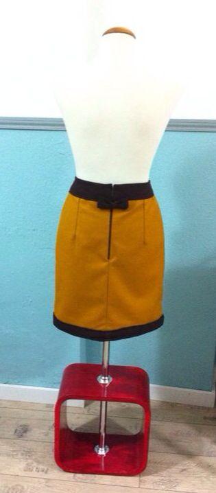 [Falda Recta] - Falda de Paño ocre con cinturilla en marrón y añadido decorativo. Forro interior ocre. Cremallera vista marrón trasera y lazo decorativo marrón en el cierre.
