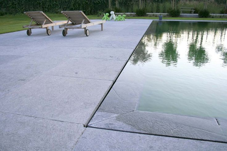 Swimming pool with a water surface that is level with the patio. Great detail! Grote strakke tuinen | Filip Van Damme