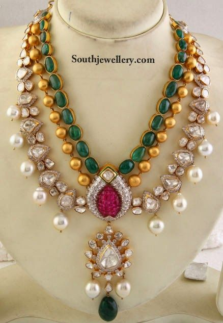 This gorgeous kundan jadau haar is by Khurana Jewellers. This necklace features an emerald studded chain followed by a chain of gold balls, followed by kundan chain studded with uneven shaped polki with south sea pearl drops. All these chains attached to a central pendant studded with kundans, carved ruby, south sea pearl drops and emerald drop
