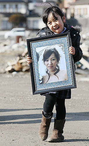 Five-year-old Marin Sasaki poses with a portrait of her late mother, who lost her life in the Great East Japan Earthquake and tsunami a year ago, in Kesennuma, Miyagi Prefecture, on March 11, 2012, the first anniversary of the disasters. At 2:46 p.m., the exact time the earthquake struck last year, Marin held her hands in prayer as she stood at the exact place where her mother's body was found. For the past year, she tried her best not to speak of how much she missed her mother, according to…