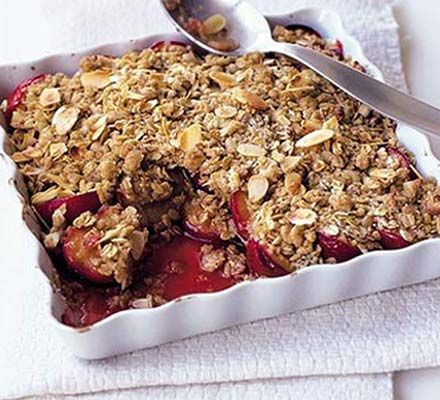 ipe plums , halved, stone removed  4 tbsp maple syrup  50g butter , cut into pieces  50g plain flour  50g rolled oats  25g golden caster sugar  ½ tsp ground cinnamon  25g flaked almonds