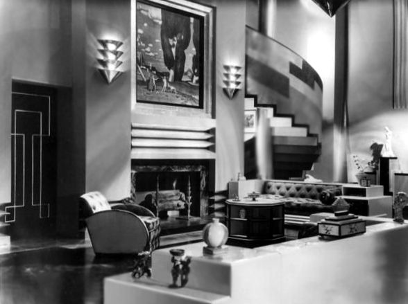 The art deco interior of a house which serves as the set for the film our modern maidens with a sweeping staircase leading from the lounge area