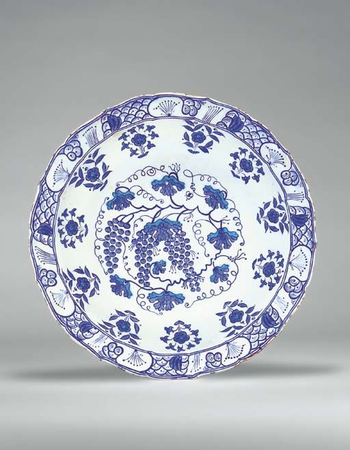 AN IZNIK BLUE AND WHITE POTTERY DISH OTTOMAN TURKEY, CIRCA 1540 With cusped sloping rim on short foot, the white interior painted in cobalt-blue and turquoise with three bunches of grapes on the vine, the scalloped leaves issuing scrolling tendrils, the cavetto with floral sprays, the rim with stylized wave and rock design, the exterior with similar floral sprays to those on the cavetto, intact, 14¾in. (37.2cm.) diam.