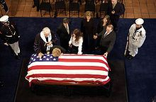 Nancy Reagan leans her head on her husband's casket at his presidential library