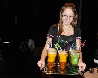 """Students in the event management program at the Lloydminster campus created their own """"mock restaurants"""" complete with menu, wardrobe and ambiance for their food and beverage assignment. Ashley Fadden is pictured here serving rootbeer and coke floats in their 1950s family-style Lightning Diner."""