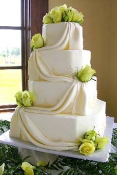 This four tier wedding cake is cross between a square and hexagon shape. Free flowing fondant is draped from one tier to the next with yellow roses as the wedding cake topper. - From www.thecakestudio.net