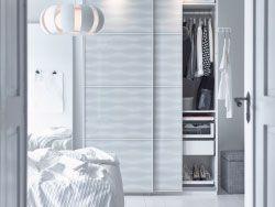 Makuuhuone, jonka valkoisessa vaatekaapissa kuvioidut lasiliukuovet.