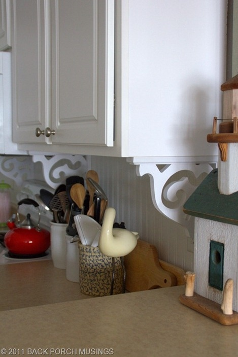 To add character to a kitchen, use bead board or bead board wall paper and brackets.
