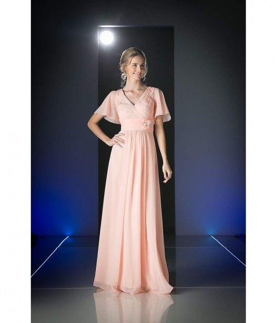 Dreamy and gorgeous! This beautiful pleated empire waist gown is accented with a ruched flower on the waistline. This light pink long dress is complete with alluring v-neck and flowing short sleeves.