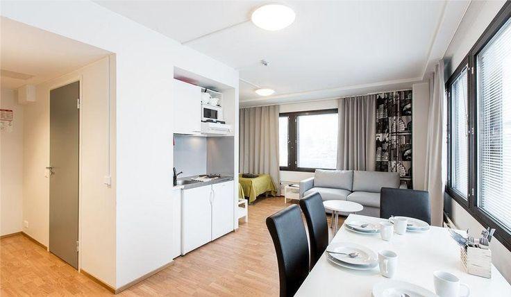 Квартира-студия в Хельсинки. Мини-кухня, белый интерьер, темные шторы, яркий текстиль.