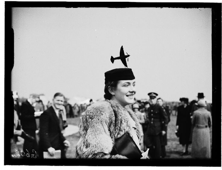 A photograph of Miss Babs Smith wearing a hat decorated with a miniature aeroplane, taken in May 1938 by George W Roper for the Daily Herald.    Miss Smith was attending the Royal Aeronautical Society's Garden Party, held at Fairey Airfield, Harmondsworth, Middlesex.