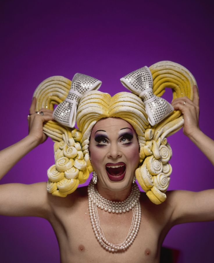 Wig, 'Pretty Pony', sponge foam/acrylic paint/ glitter/wire/fabric, Michael Gates, Australia, 1995. Wig made from strips of sponge foam with chicken wire base, in the form of two pony tails with silver and white ribbon ties, painted in yellow and white acrylic paint with glitter applied. Fabric lini...