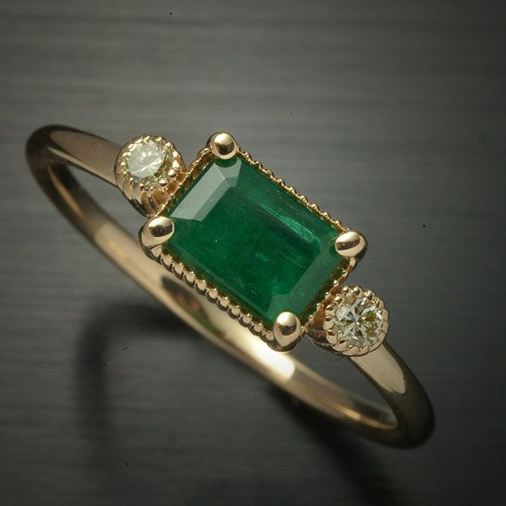 Natural emerald Solitaire with 2 light yellow diamonds ring 14kt white or yellow gold The Emerald is Natural from Zambia treated with oil with Lots of color weights .55ct 2 small diamonds on the side 1.7mm 14kt pink gold setting polished This ring is great for a gift. Finger size is 5.5 but can be sized. All my jewelry is designed and manufactured at two family owned local manufacturing shops in NYC and my jewelry only uses Conflict Free Diamonds from reputable diamond dealers with Kimberly…
