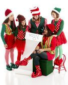 A family of Christmas elves is happy to read Santa Claus list Stock Image